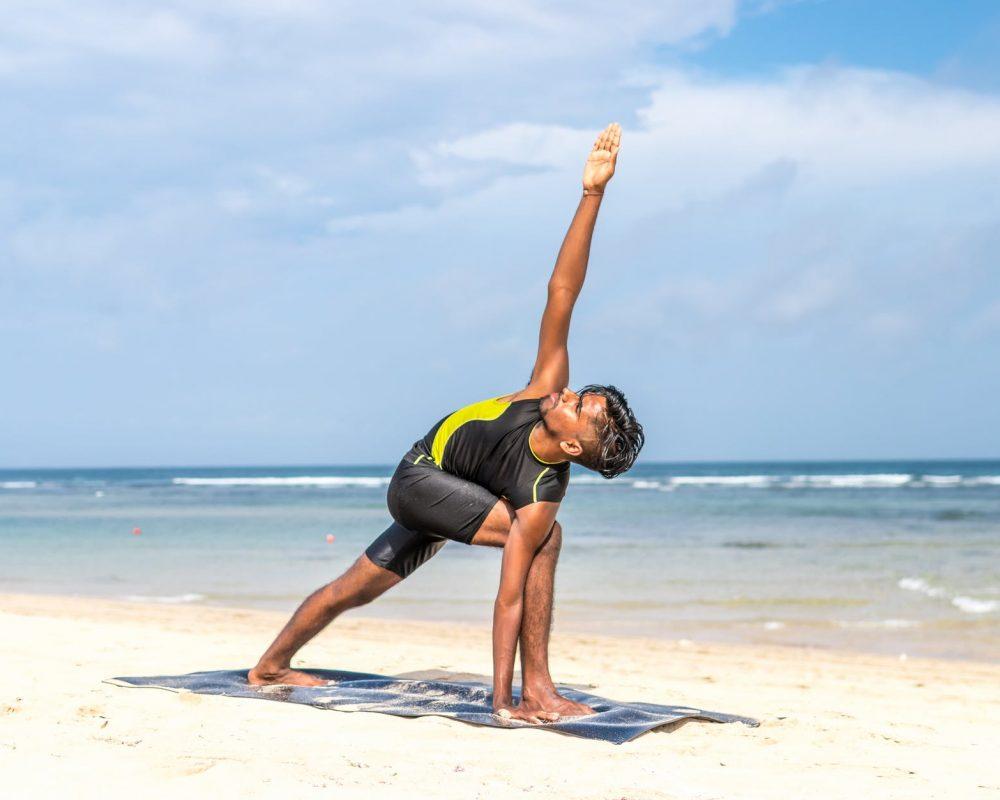 man doing yoga pose on blue mat beside seashore