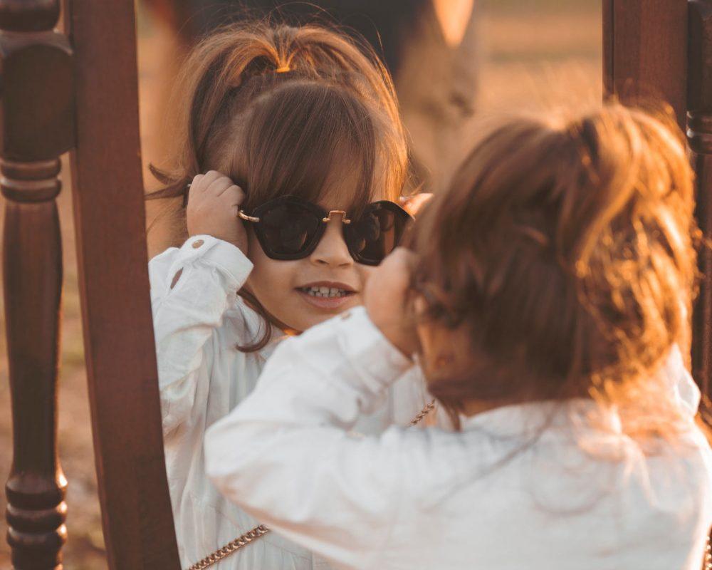 girl in white long sleeved shirt wearing sunglasses facing mirror